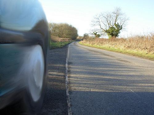 Primer plano de la rueda de un coche que circula cerca de una línea longitudinal continua. Fotomontaje