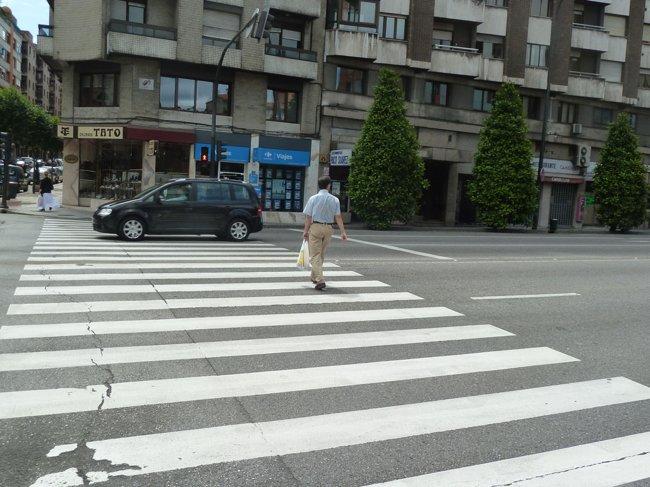 Semáforo en rojo y peatón cruzando